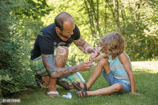 Father cleans boys wound with antiseptic in preparation for a sticking plaster. Wound is visible. The mans arms and leg are tattooed. Background of green trees, bushes and grass