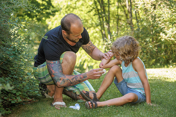 dad gives first aid stock photo