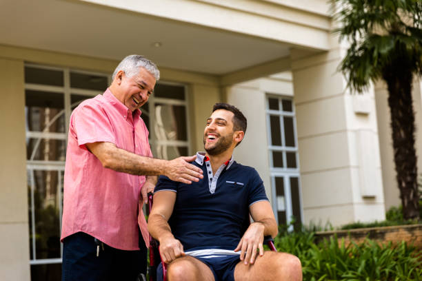 Dad helping his son sitting in his wheelchair People collection paraplegic stock pictures, royalty-free photos & images