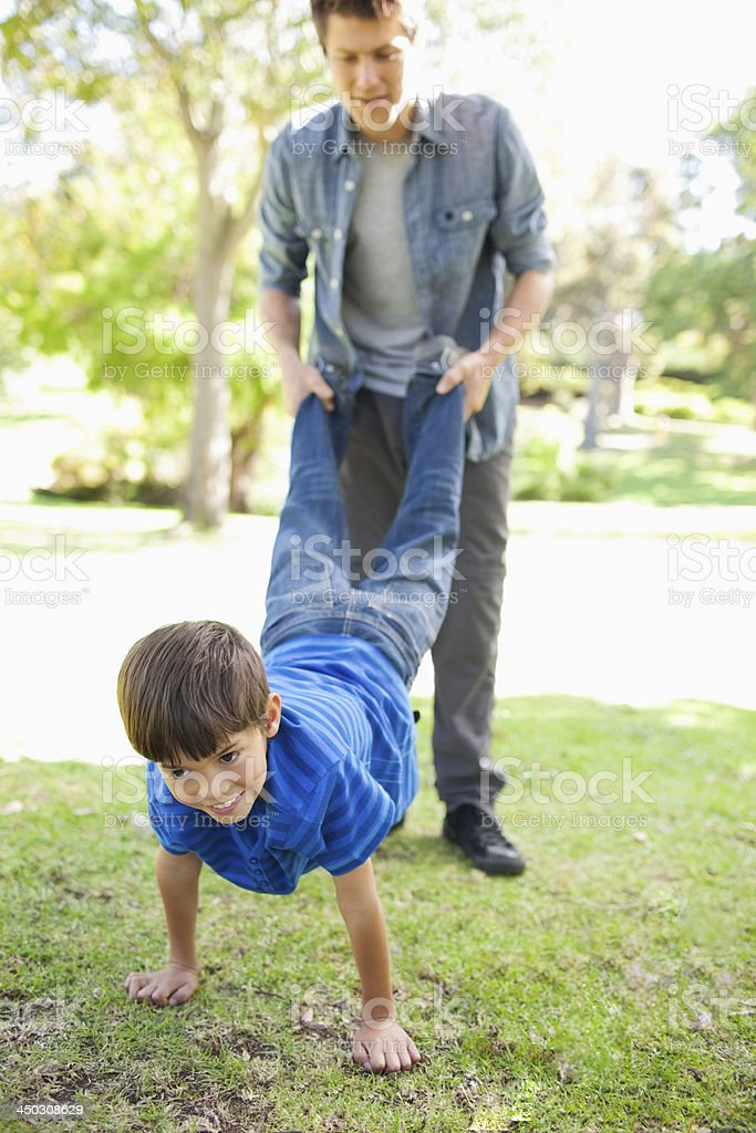 Dad helping his son walk on the hands stock photo