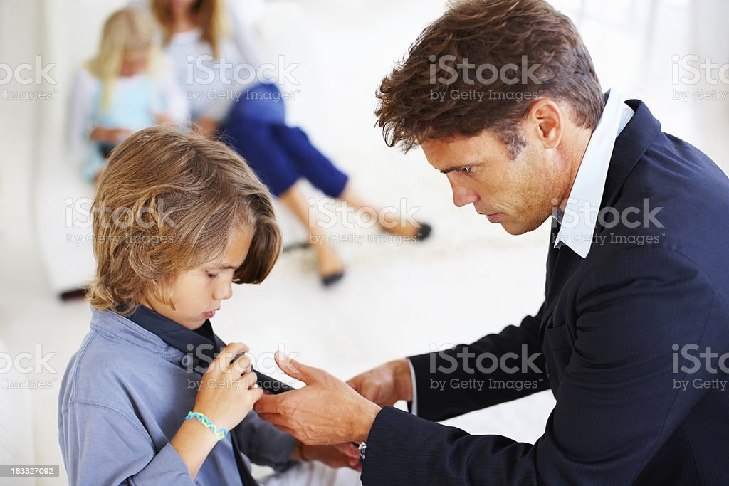 Dad helping son get dressed royalty-free stock photo