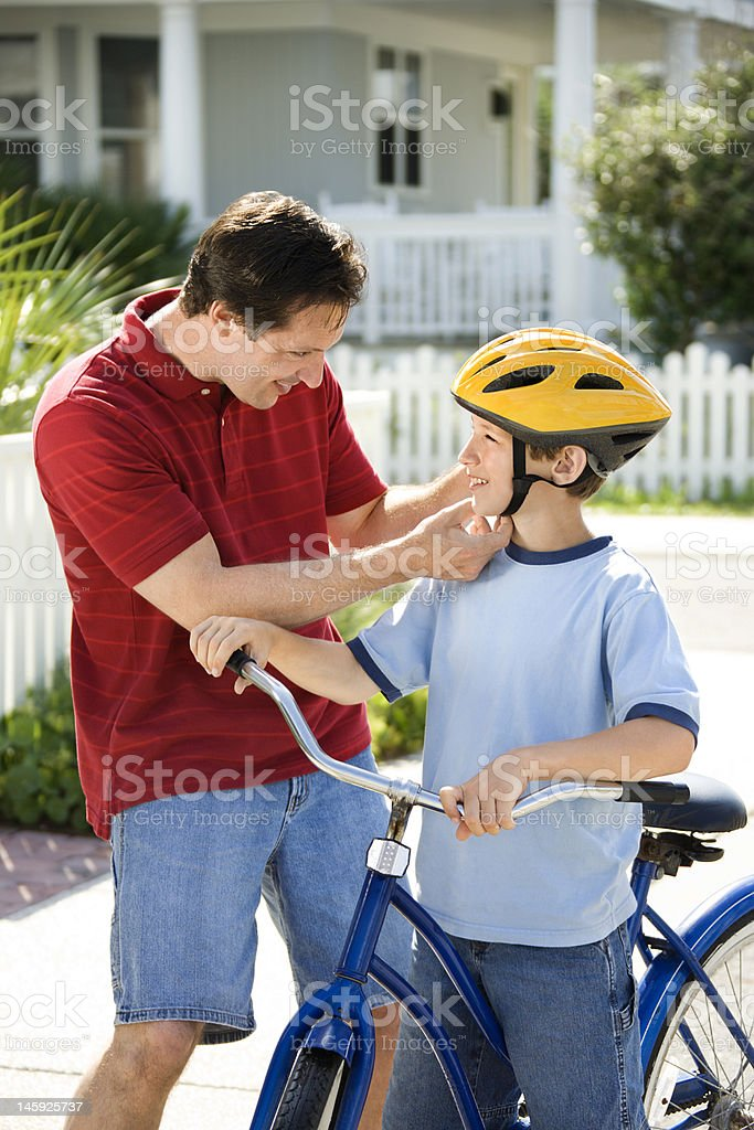 Dad helping son with bike helmet. stock photo