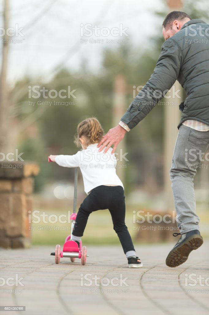 Dad helping young daughter learn to ride scooter royalty-free stock photo