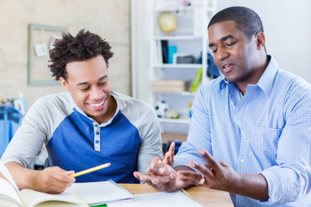 Dad helps teenage son with homework stock photo