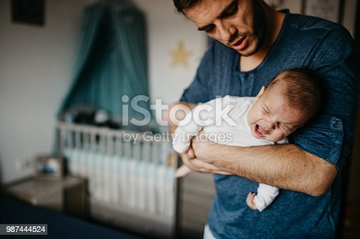 Dad Holding crying baby in the colic carry