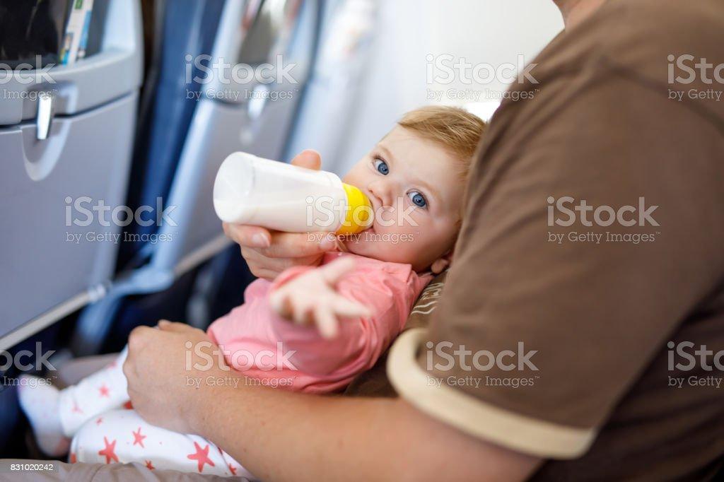 Papa hält seine Tochter während des Fluges im Flugzeug in den Urlaub gehen – Foto