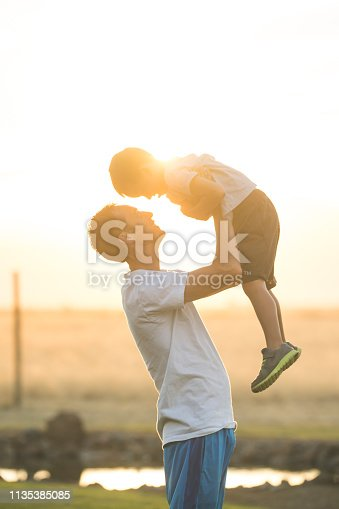 An ethnic dad holds his elementary-age son up in the air playfully outside. They're in an outdoor grassy area and have just completed a workout together.