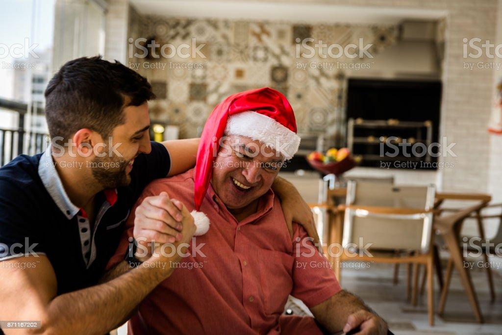 Pai no chapéu de Papai Noel usando tablet digital e filho se divertindo em casa - foto de acervo