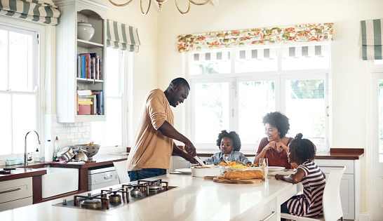 Shot of a cheerful young family preparing food in the kitchen together at home during the day