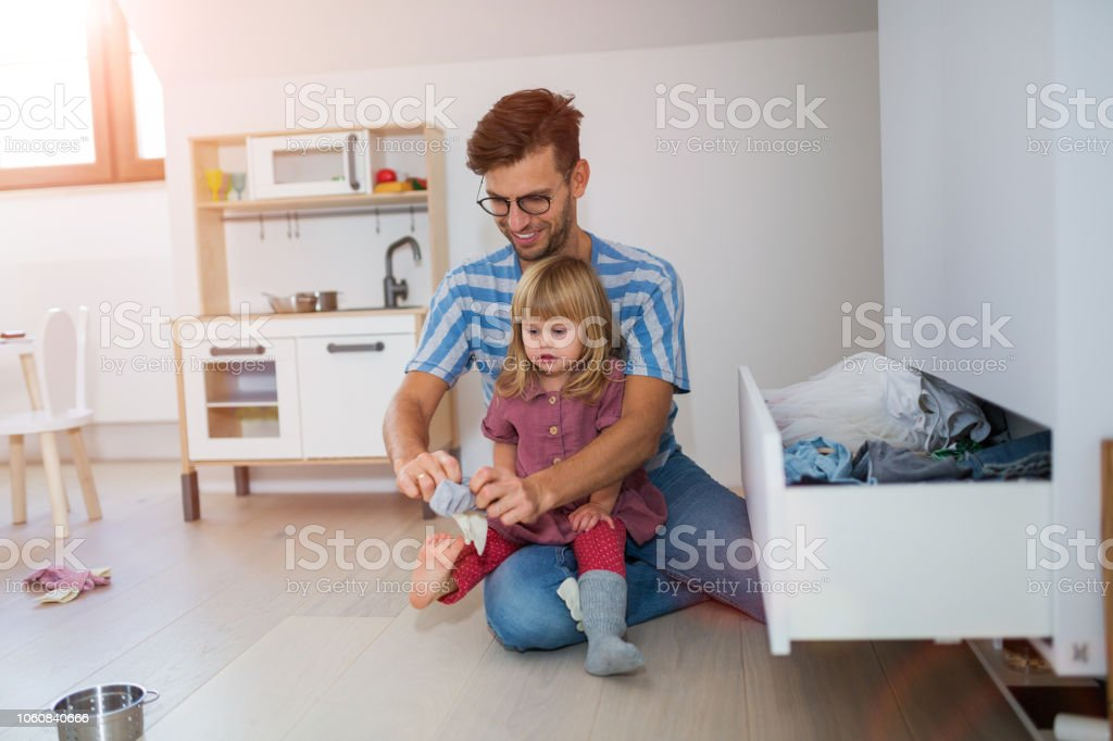 Dad is helping toddler daughter to get dressed stock photo