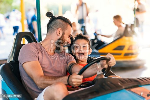 Photo of Caucasian young hipster Father and his 5 years old son having a ride in the bumper car at the amusement park during summer day. Happy family leisure in holiday weekend