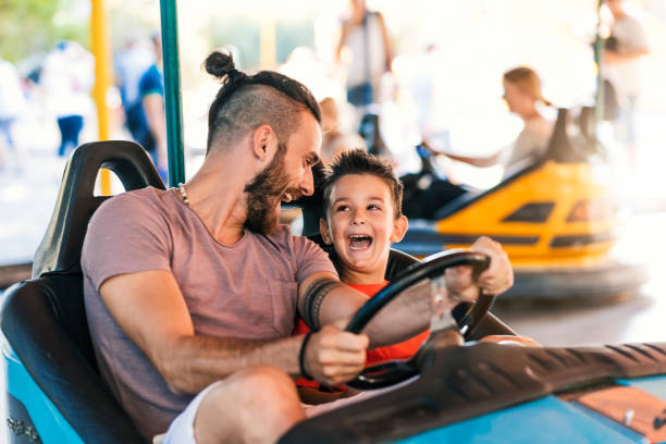Dad is his best friend Photo of Caucasian young hipster Father and his 5 years old son having a ride in the bumper car at the amusement park during summer day. Happy family leisure in holiday weekend traveling carnival stock pictures, royalty-free photos & images