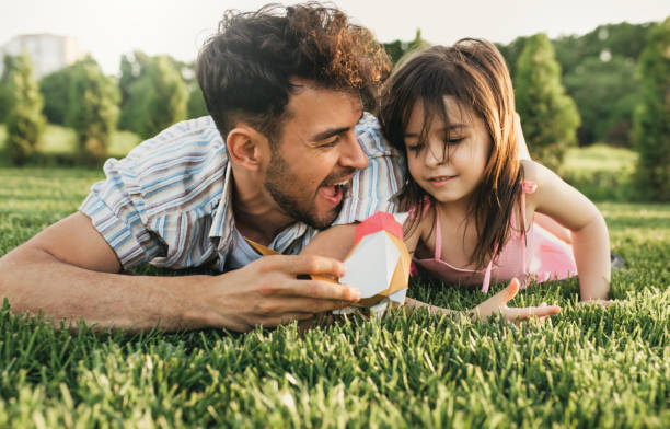 Dad is spending time with his child lying on the green grass outdoors. Happy cute little girl playing with her father in the park with a bird toy. Happy father's Day. Daddy and daughter shares love. stock photo