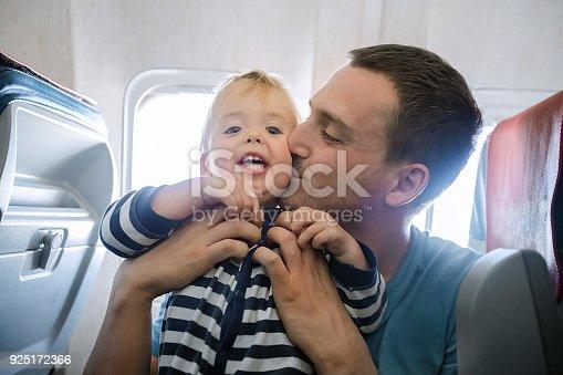 istock Dad kisses his son on the plane interior 925172366