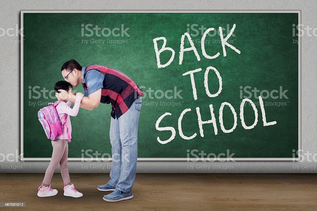 Padre besando a su hija en la clase - foto de stock
