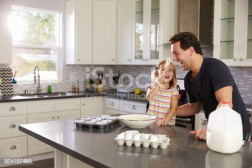 istock Dad laughs as girl puts cake mix on his nose in the 524157460