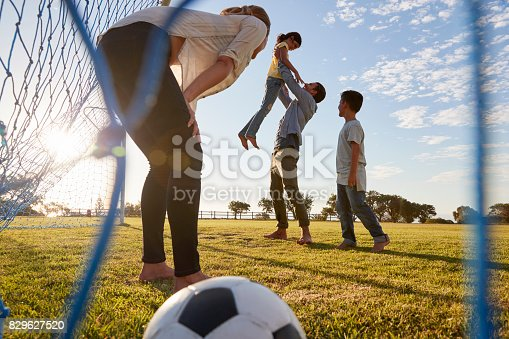 829627936istockphoto Dad lifts his daughter during a family football game 829627520