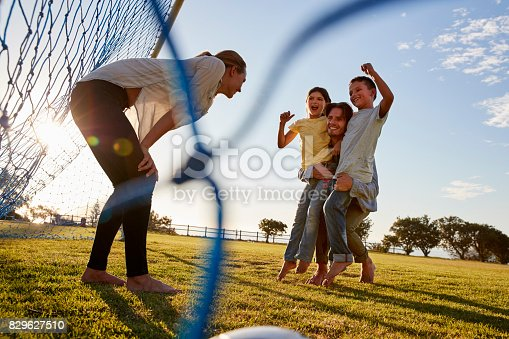 829627936istockphoto Dad lifts his son and daughter during a family football game 829627510