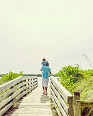 Man carries a toddler on his shoulder walking down a scenic beach boardwalk. Man is African American, tender moment of togetherness between father and son
