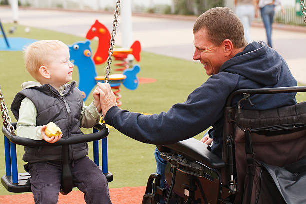 Dad play with child. Disabled Father play with his little son on the playground. paraplegic stock pictures, royalty-free photos & images