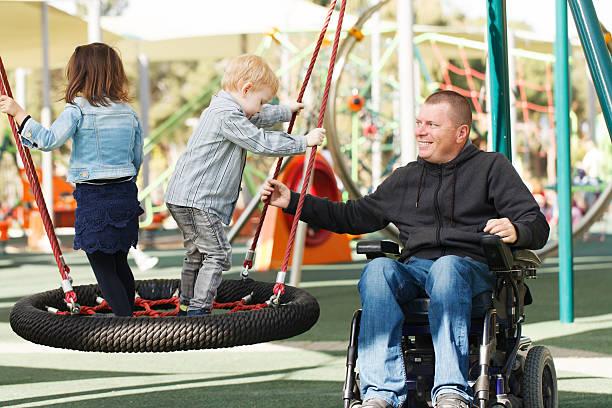 padre gioca con figlio e figlia - sedia a rotelle foto e immagini stock