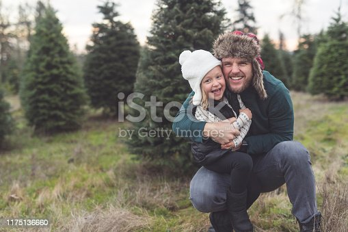 A young bearded dad playfully poses for the camera with his daughter, whom he is holding while he crouches down amidst the trees at a Christmas tree farm.