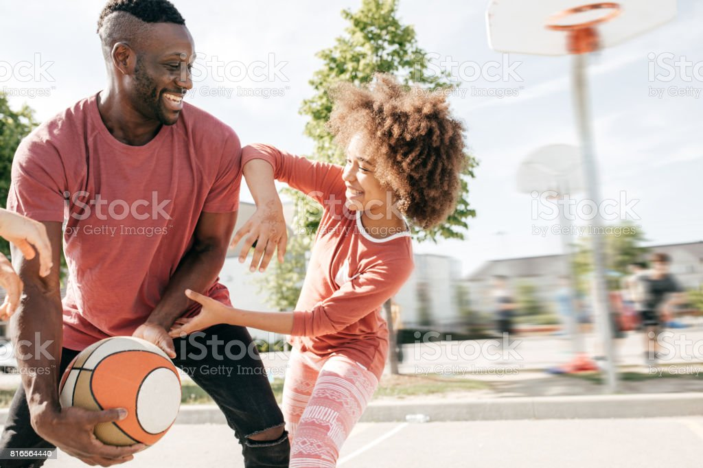 Dad playing basketball with daughter stock photo