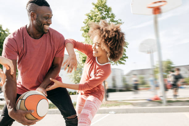 Dad playing basketball with daughter Dad playing basketball with daughter basketball sport stock pictures, royalty-free photos & images