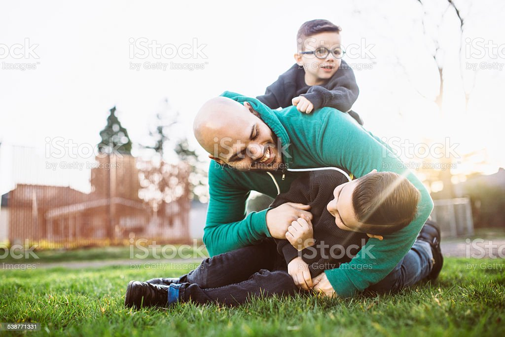 Dad Playing Outside with His Boys stock photo