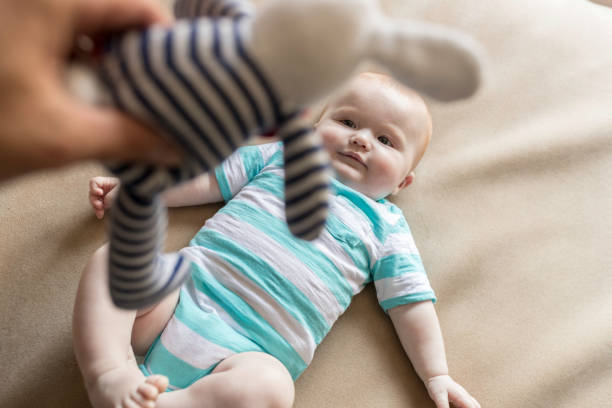 POV Dad Playing with baby Boy and Plush on Bed stock photo