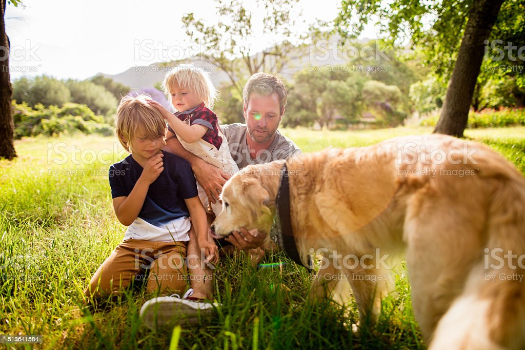 Dad plays with his cute sons and their dog outside stock photo