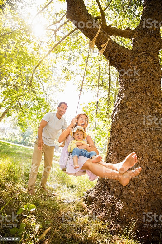 Dad pushing mom and their little girl on a swing stock photo