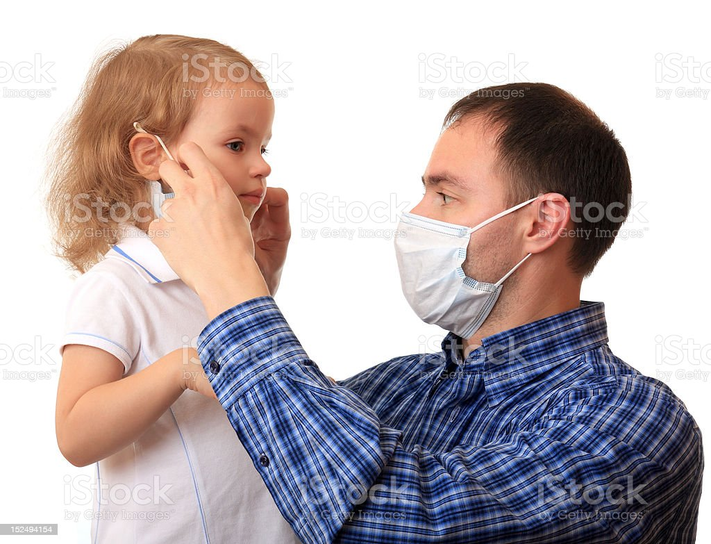 Dad puts a medical mask on to daughter royalty-free stock photo