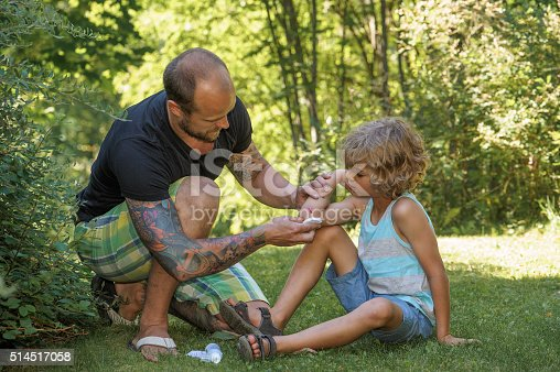 Father cleans boys wound with antiseptic in preparation for a sticking plaster. Wound is visible. The mans arms are tattooed. Background of green trees, bushes and grass