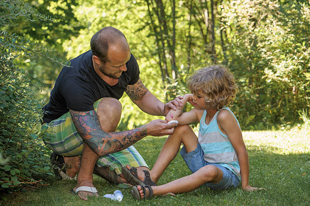 dad puts antiseptic on sons elbow stock photo