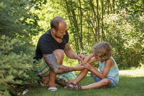 dad puts plaster on sons elbow stock photo