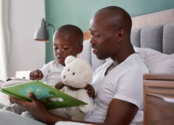 Dad reading bedtime stories to son