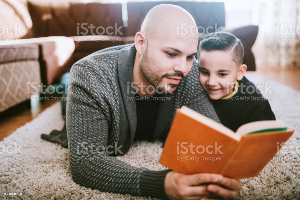 Dad Reading to Son in Living Room stock photo