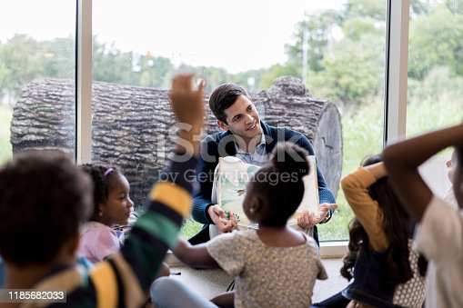 Confident kindergarten teacher or parent reads to a group of children.
