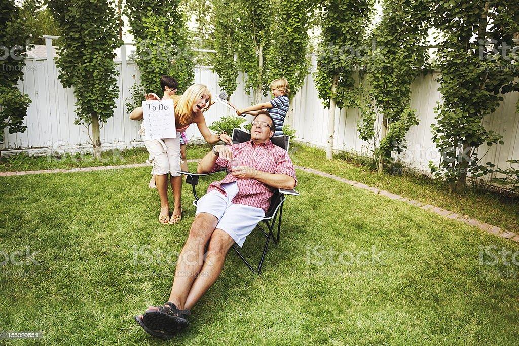 Dad relaxes amid family hubbub stock photo
