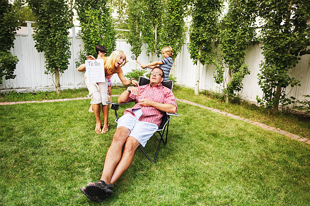 Dad relaxes amid family hubbub stock photo