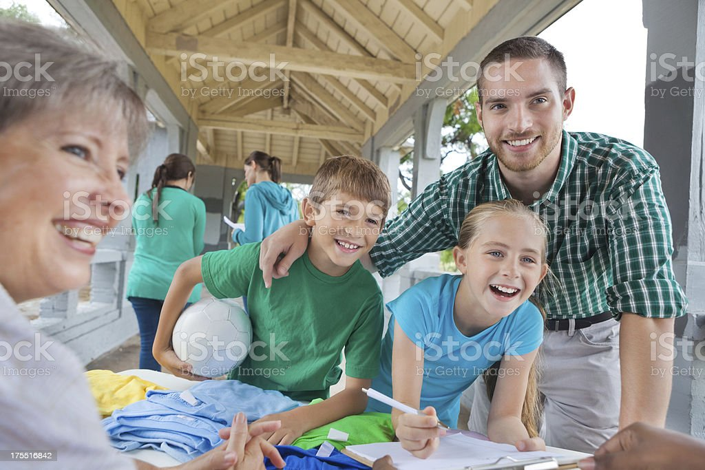 Dad signing kids up to play soccer or team sport royalty-free stock photo