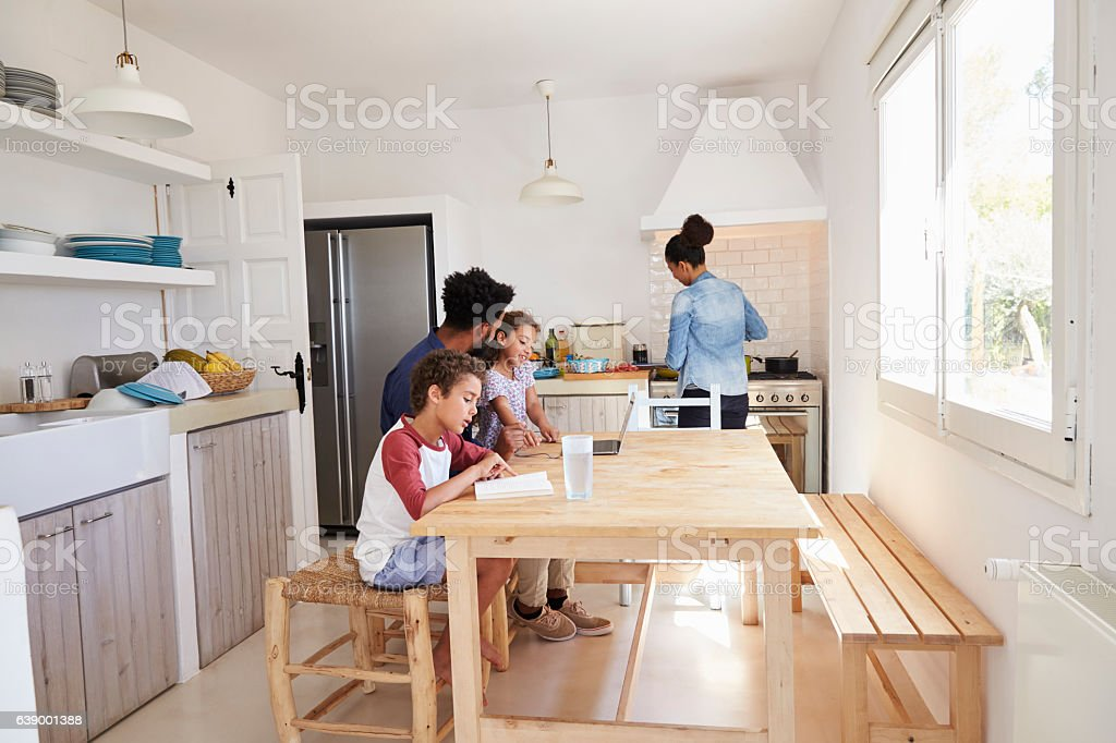 Dad sitting with kids at kitchen table while mum cooks stock photo