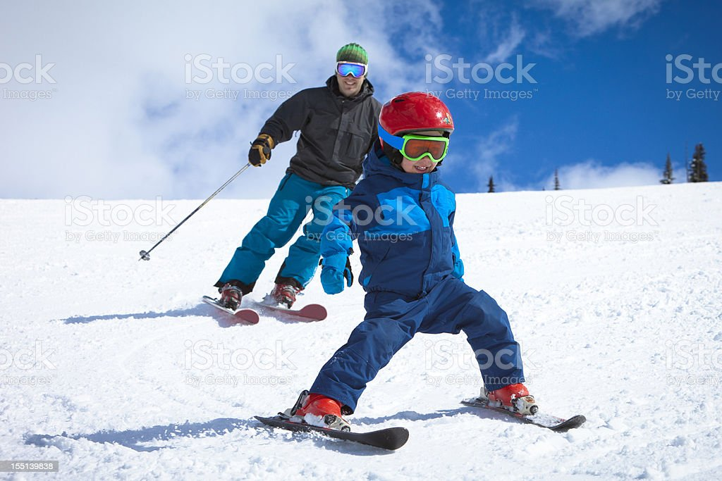dad skiing with his small child. stock photo