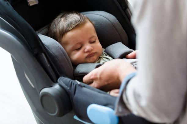 le papa attache le bébé dans le siège d'auto - child car sleep photos et images de collection