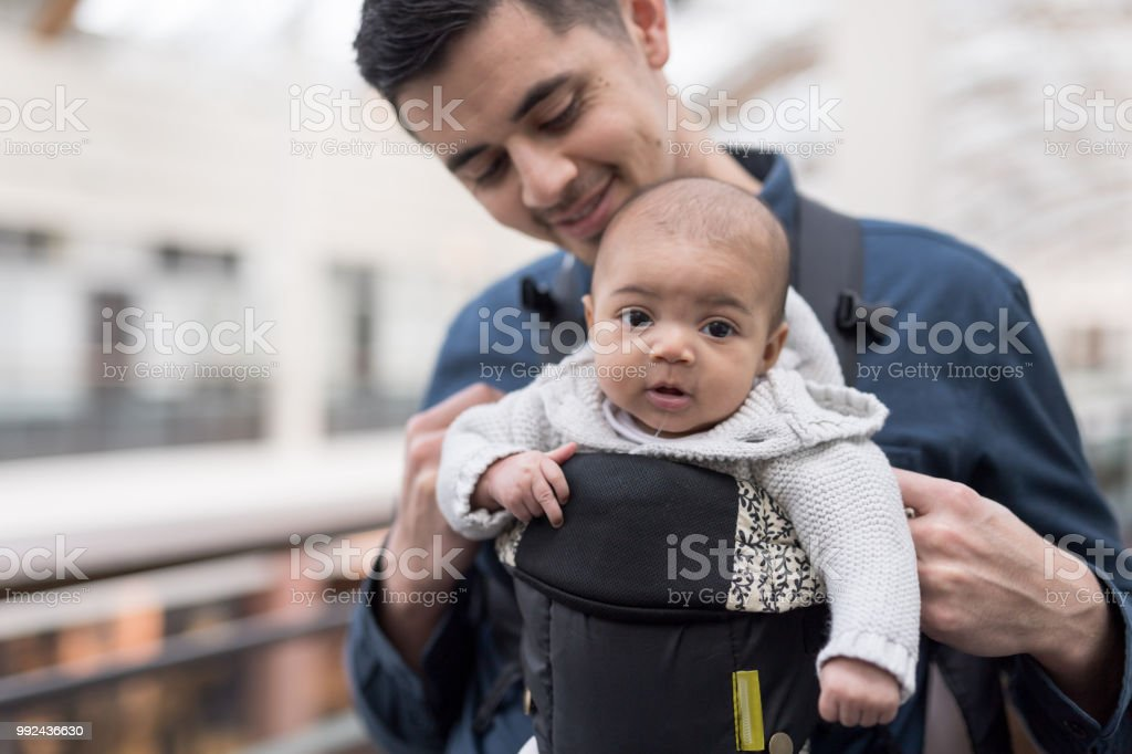Dad takes his newborn daughter to the mall in a baby carrier A handsome ethnic dad carries his infant daughter in a forward-facing infant carrier. They are walking through the mall and she is soaking in all the sights and sounds and looking at the camera. 2-5 Months Stock Photo