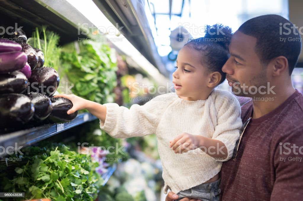 Dad takes his young daughter grocery shopping stock photo