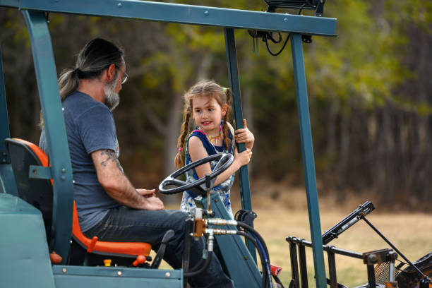 Dad taking his daughter on a tractor stock photo