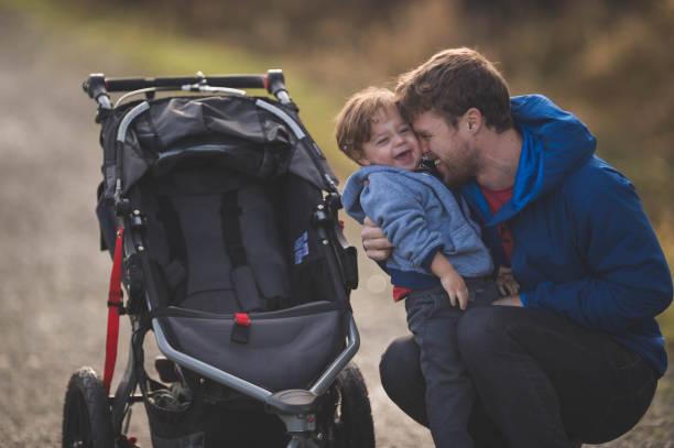 ベビーカーで散歩に息子を連れてパパ ストックフォト