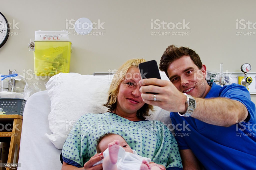 Dad taking picture of newborn and family stock photo
